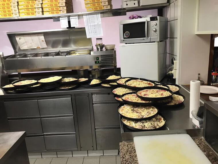 belegte Pizzen in der Küche der Pizzeria in Vilshofen
